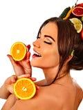 Le masque de cheveux des fruits sur la prise de tête de femme divise en deux les yeux fermés oranges Photos libres de droits