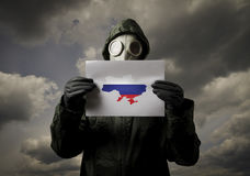 Le masque de gaz et l'Ukraine tracent avec le drapeau russe Photos libres de droits