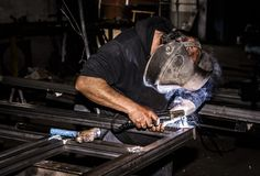 Le masque professionnel a protégé l'homme de soudeuse travaillant à l'homme de soudeuse protégé par masque de weldingProfessional photographie stock libre de droits