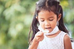 Le masque protecteur d'usage asiatique en difficulté de fille prenait la médecine de sirop photos stock