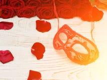 Le masque rouge de carnaval se trouve sur une table en bois blanche entourée par des pétales et un bouquet des roses Images libres de droits