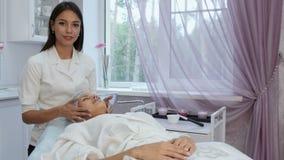 Le massösen som ger en ung kvinna ansikts- massage och talar om brunnsortbehandling arkivfilmer