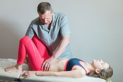 Le masseur visc?ral manuel masculin de th?rapeute soigne un jeune patient f?minin Édition de la cuisse photographie stock libre de droits