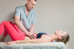 Le masseur visc?ral manuel masculin de th?rapeute soigne un jeune patient f?minin ?ditez les organes internes et l'?limination de photo libre de droits