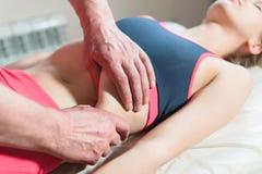 Le masseur visc?ral manuel masculin de th?rapeute soigne un jeune patient f?minin ?ditez les organes internes et l'?limination de images libres de droits