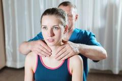 Le masseur visc?ral manuel masculin de th?rapeute soigne un jeune patient f?minin R?chauffez les ?paules et le cou photographie stock