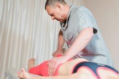 Le masseur visc?ral manuel masculin de th?rapeute soigne un jeune patient f?minin Travail avec les fesses du plus lombo-sacr? et photos stock