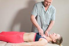 Le masseur visc?ral manuel masculin de th?rapeute soigne un jeune patient f?minin Travail avec les muscles pectoraux et le solair photos stock