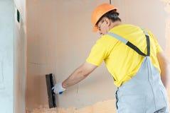 Le mastic de travailleur de la construction un mur photographie stock