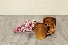 Le matin commence par du café Tasses de café d'argile avec la branche du lilas Fond concret noir photos libres de droits