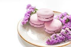 Le matin de Madame avec des macarons et le mauve fleurit le fond blanc de bureau Photo libre de droits