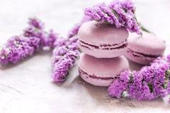 Le matin de Madame avec des macarons et le mauve fleurit le fond blanc de bureau Image stock