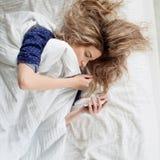 Le matin, la femme sous la couverture, arrête le réveil ou observer le réseau social photo stock
