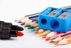 Le matite colorate e correggono l'affilatrice su fondo bianco Fotografia Stock Libera da Diritti