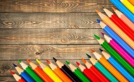Le matite colorate hanno sistemato in una fila su di legno Immagini Stock Libere da Diritti