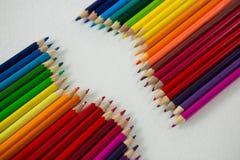 Le matite colorate hanno sistemato in una fila su fondo bianco Immagini Stock Libere da Diritti