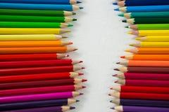 Le matite colorate hanno sistemato in una fila su fondo bianco Fotografia Stock Libera da Diritti