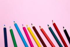 Le matite colorate senza cuciture dell'arcobaleno remano con l'onda dal lato più basso, parecchie disposizioni, su carta rosa Con fotografia stock libera da diritti