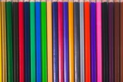 Le matite colorate sono disposte nelle file fotografie stock libere da diritti