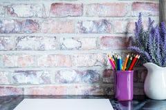 Le matite colorate in una tazza, vaso di lavanda fiorisce, Libro Bianco su una tavola contro un muro di mattoni Immagini Stock