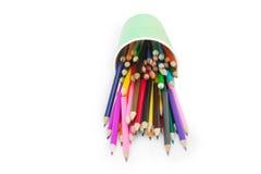 Le matite di colore cadono dal vetro verde di plastica Immagini Stock
