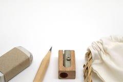 Le matite, le gomme, i temperamatite ed il tessuto insaccano Immagine Stock
