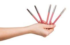 Le matite per il labbro di uso allineano in mani femminili isolate Immagine Stock