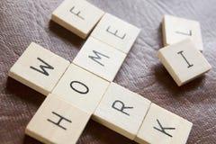 Le mattonelle di legno nelle parole incrociate modellano le parole Hom di ortografia Fotografia Stock