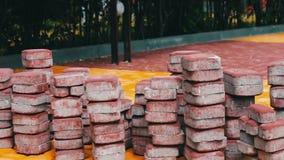 Le mattonelle multicolori del marciapiede nel parco del ` s dei bambini si trovano sulla terra pronta per porre stock footage