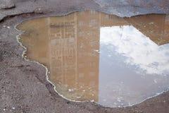 Le mauvais a asphalté la route avec un grand nid de poule rempli avec de l'eau Assiette de la route détruite dangereuse photo stock