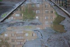 Le mauvais a asphalté la route avec un grand nid de poule rempli avec de l'eau Assiette de la route détruite dangereuse photos stock