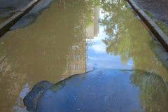 Le mauvais a asphalté la route avec un grand nid de poule rempli avec de l'eau Assiette de la route détruite dangereuse images stock