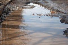 Le mauvais a asphalté la route avec un grand nid de poule rempli avec de l'eau Assiette de la route détruite dangereuse photos libres de droits