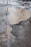 Le mauvais a asphalté la route avec un grand nid de poule rempli avec de l'eau Assiette de la route détruite dangereuse photo libre de droits