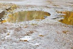 Le mauvais a asphalté la route avec un grand nid de poule rempli avec de l'eau Assiette de la route détruite dangereuse Réflexion photos libres de droits