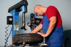 Le mécanicien change un pneu Photographie stock libre de droits
