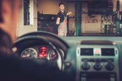 Le mécanicien de voiture souhaite la bienvenue au nouveau client à son service des réparations automatique Images stock