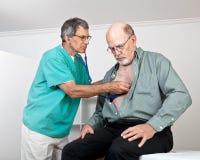Le médecin ou l'infirmière écoute le coeur du patient plus âgé Image stock