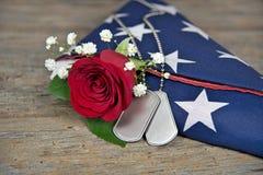Le medagliette per cani militari e sono aumentato sulla bandiera piegata Immagini Stock Libere da Diritti