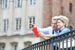 Le medelålders manvisning något till kvinnan med resehandboken i stad fotografering för bildbyråer