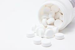 Le medicine bianche scorrono dal contenitore. Fotografia Stock