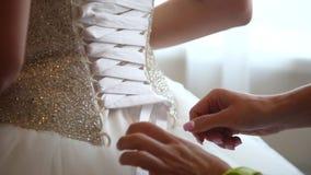 Le meilleur ami aide la future jeune mariée à porter une robe de mariage closeup banque de vidéos