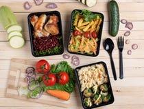 Le melanzane fritte in contenitore con le ali di pollo arrostite sopra kitcen il bordo, i pomodori, lo zucchini ed i micro greens immagini stock