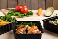 Le melanzane fritte in contenitore con le ali di pollo arrostite sopra kitcen il bordo, i pomodori, lo zucchini ed i micro greens fotografia stock