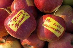 Le mele con natale felice desidera in due lingue Fotografia Stock