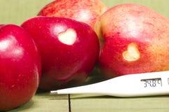 Le mele rosse fresche con un cuore hanno modellato il ritaglio ed il termometro sopra Immagini Stock Libere da Diritti