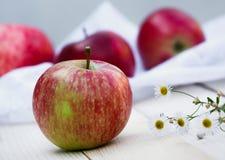 Le mele rosse si trovano su un fondo di legno leggero Immagine Stock Libera da Diritti