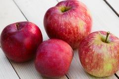 Le mele rosse si trovano su un fondo di legno leggero Immagini Stock Libere da Diritti