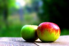 Le mele variopinte sullo scrittorio di legno si imbarcano con copyspace per voi sul testo o sul logo Fotografia Stock
