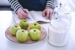 Le mele verdi su un piatto per fare una torta e la ragazza scrive un reci Immagine Stock Libera da Diritti